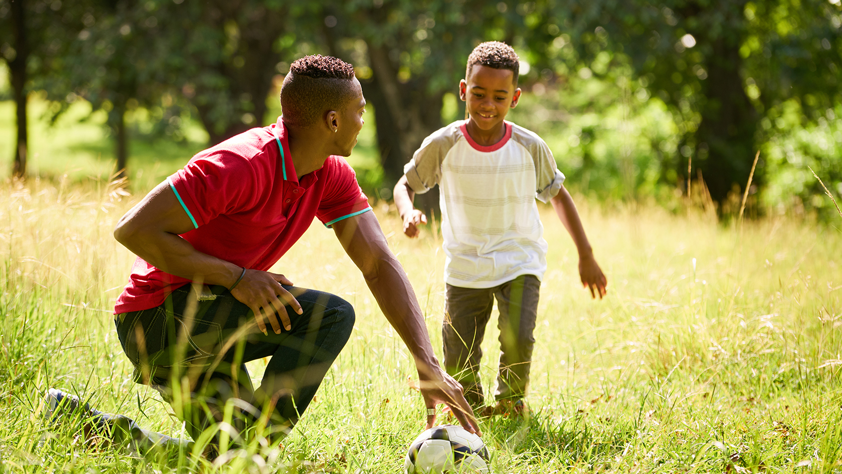 A boy and dad playing football